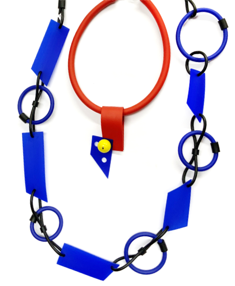 A short collar with a cut rubber pendant. A long necklace with cut rubber and rings.
