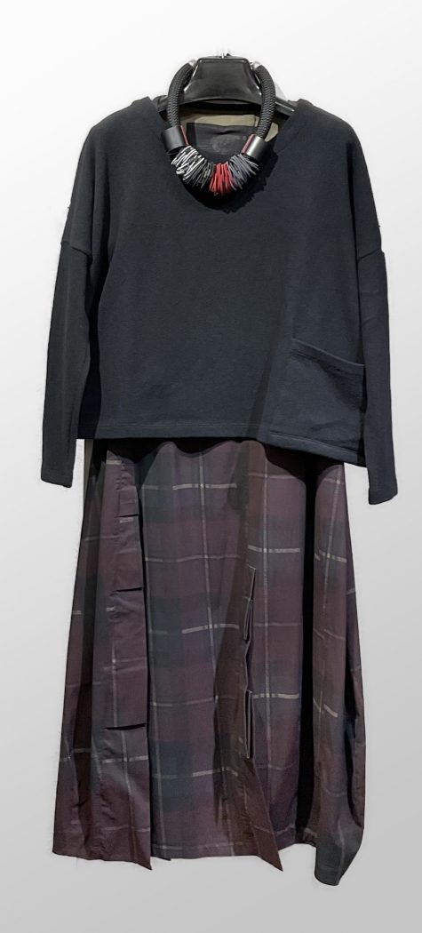 Mes Soeurs et Moi cozy knit boxy top in black, layered with a Rundholz Black Label bubble dress in tartan-print technical fabric.