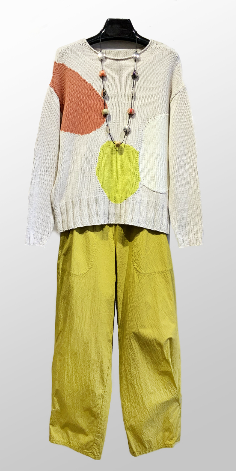 Oska relaxed knit sweater with pastel patches, over a pair of Oska lightweight cotton trousers.