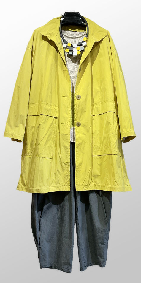 Mycra Pak lemon yellow big raincoat, over an Oska cotton sweater with big dots. Paired with Oska relaxed cotton trousers.